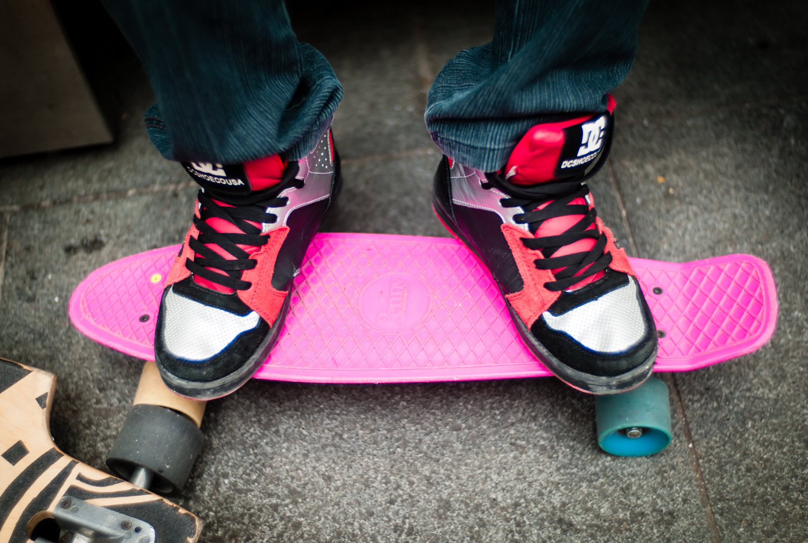 A boy's sneakers and skateboard