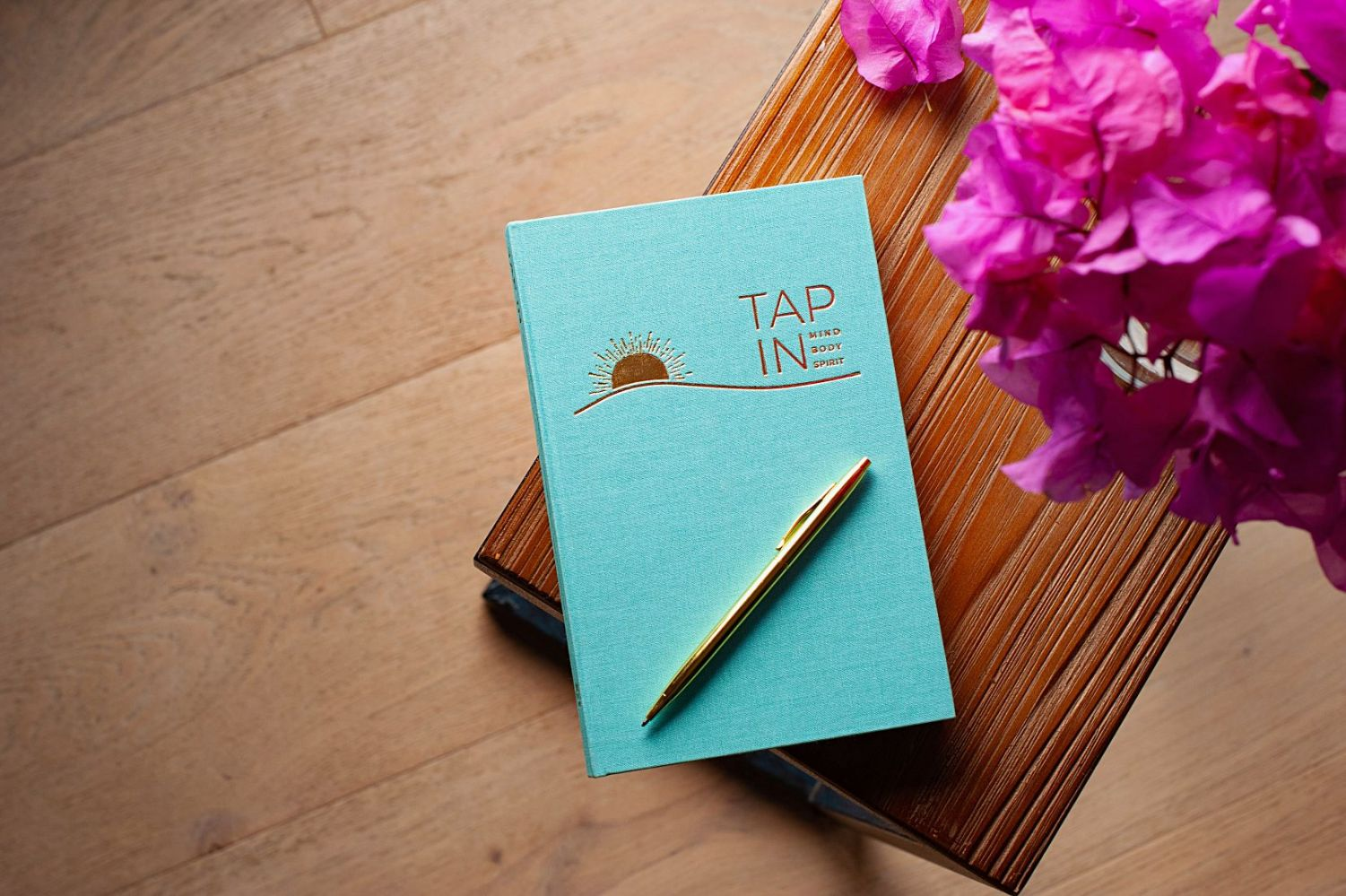 TAP IN wellness journal has a seafoam blue linen cover and gold foil writing