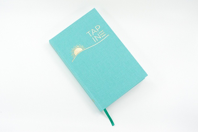 TAP IN wellness journal on a white background.