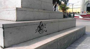 Grafiti vandálico en el pedestal de la estatua pedestre de Simón Bolívar, en su plaza homónima de Valera. Bien cultural venezolano en riesgo. Alerta cultural.