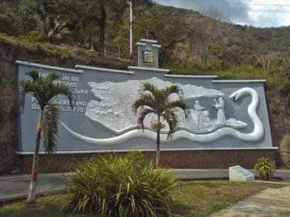 Chaguaramos jóvenes acompañan el mural de entrada de San Antonio de Capayacuar. Patrimonio cultural del estado Monagas, Venezuela.