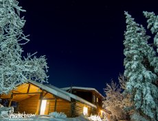 A cabin is lit up during dark, clear, and very cold night in Fort Yukon, Alaska.