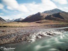 A glacial stream flows out of the mountains near Atigun Pass, Brooks Range, Alaska