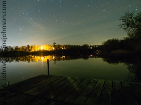 The starry night was reflected perfectly in the lake. The only thing that discerns the the earth is the the dock.