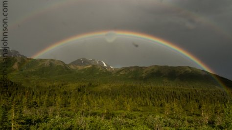 A rainbow arches over the mountains along the Richardson Highway.