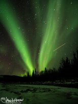 A plane streaks through the aurora over the Chena River.