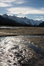 Mountains behind the braids of a shallow portion of the river.
