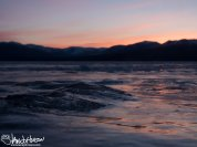 The sunrise at Kluane Lake bounces off the ice.