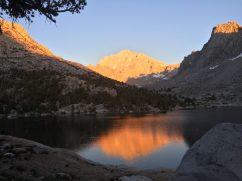 Sun setting against the mountains, turning them a blazing orange.