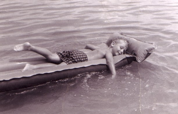 Yours Truly beats the heat on an inflatable air mattress, about 1962