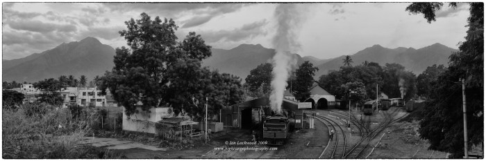 View form Mettupalayam train station looking north to the slopes of the Nilgiri Hills. The famous Nilgiri Mountain railway with its stem engine is warming up for the morning ride up to Conoor. Composite digital image taken in 2009.