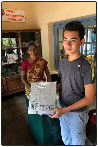 Lenny, in the midst of his MYP personal project research on endemism in Sri Lanka, gets a shirt on endemic birds of India from Stella at the Anamalais Nature Information Centre.