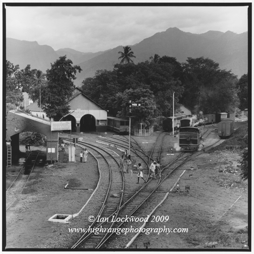 A steam locomotive warms up at Mettupalayam station overshadowed by the Nilgiri Hills.