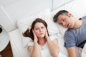 Woman lying in bed with hands over ears whilst her partner snores next to her