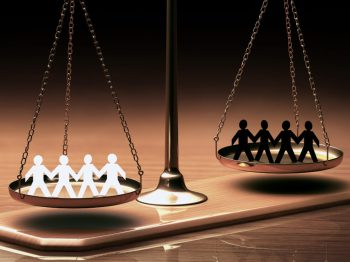 old fashioned balance scale w white stick people on one side and black ones on the other