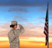 woman in camo salutes flag at sunset