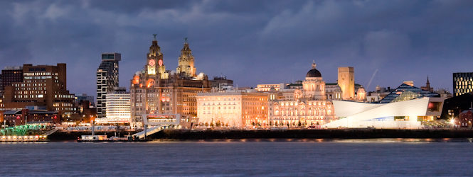 """LIVERPOOL SKYLINE AT NIGHT FROM WOODSIDE Liverpool waterfront, on the River Mersey. Including Museum of Liverpool and """"Three Graces"""", Royal Liver Building, Cunard Building and Port of Liverpool Building. Pier Head Liverpool, viewed from the Wirral Peninsula, at night. CC-BY John Hickey-Fry https://flic.kr/p/nY7KpH"""