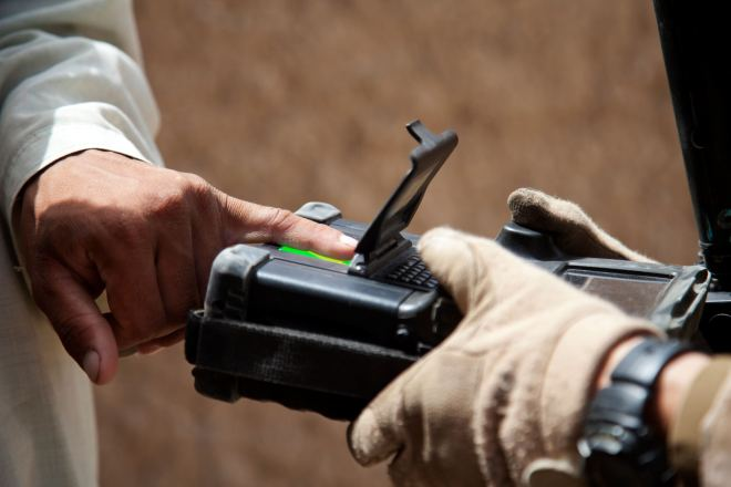 An Afghan man is finger printed using a secure electronic enrollment kit by U.S. Marine Corps Capt. Bob J. Sise, right, from Wrightsville Beach, N.C., and assigned to Georgian Liaison Team-9, during Operation Northern Lion in Mohammadabad, Helmand province, Afghanistan, June 24, 2013. Northern Lion was a Georgian-led operation conducted to deter insurgents, establish a security presence, and gather human intelligence in the area. (U.S. Marine Corps photo by Cpl. Alejandro Pena/Released)