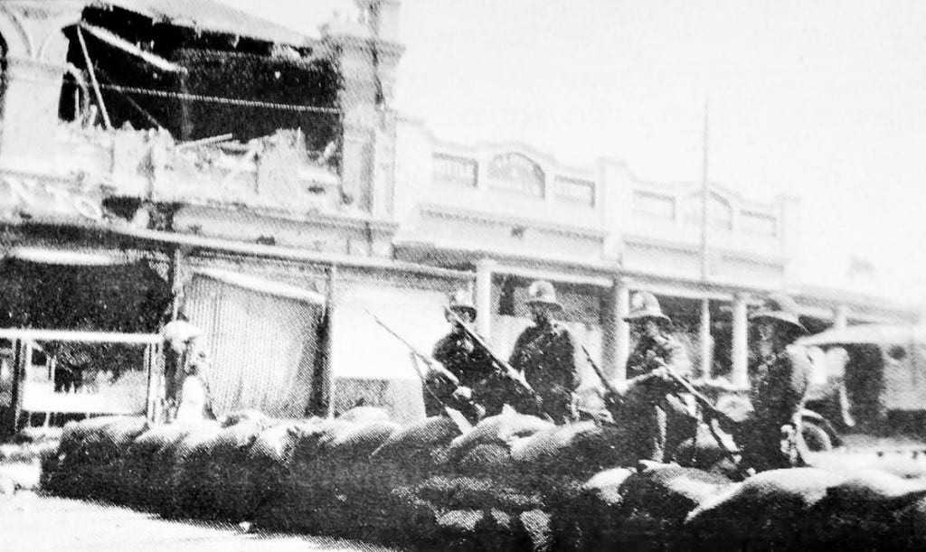 Soldiers by a barricade in Johannesburg.Bomb damage is clearly visible in the background. www.theheritageportal.co.za