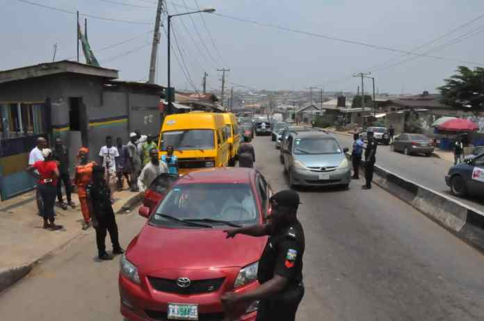 Police officers block road and checking vehicles at Ile-Iwe, bus stop, along Ekoro