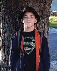 Photo of Shane Laycock, a boy with light skin photographed next to a large tree. He is wearing a backpack, a fedora, and a Superman T-shirt.