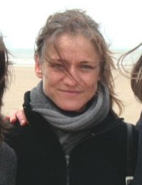 Photo of Tine Nys, a blonde woman in a jacket and scarf. Her hair is escaping from a messy ponytail and being blown across her face by the wind.