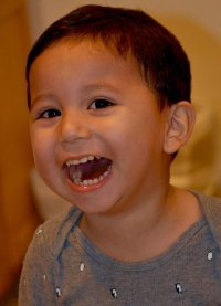 Photo of Jose Castillo-Cisneros. He is a toddler boy with tan skin and short black hair, smiling with his mouth wide open.
