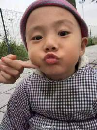 Photo of Jia Jia. He is a Chinese toddler dressed in a heavy coat and hat. An adult is pushing his chin up with a finger to make him look at the camera. He has his lips pursed as though he is kissing the camera.