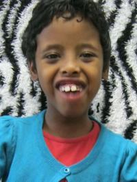 Photo of Nawaal Sayid, a girl with brown skin and short wavy black hair. She is wearing a red shirt and turquoise sweater.