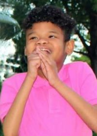 Photo of Ty Lee. He is a boy with medium-brown skin and curly black hair, wearing a hot pink T-shirt.