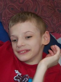 Photo of Austin Anderson, a thin boy with fair skin and dark blond hair. He is holding a hand near his face and smiling.