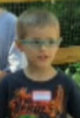 Photo of Daniel Schlemmer, a young boy wearing glasses and a navy blue T-shirt. He has fair skin and blond hair.