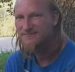 Photo of James Thomas, taken outside by the trunk of a big tree. He is a white man with blond hair and a scruffy beard.