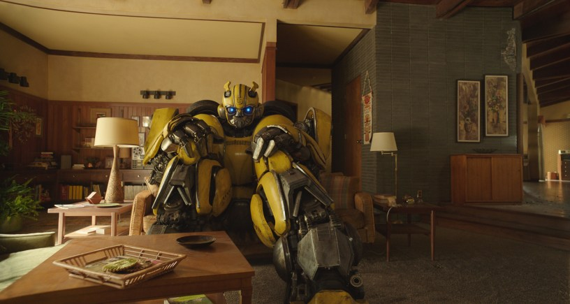 Bumblebee, an OG Transformer, sits on a couch in the 1980s, in the Transformers prequel BUMBLEBEE (2018)