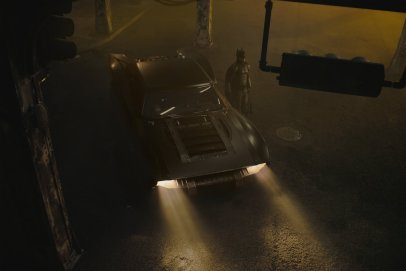 Dressed in his batsuit, Robert Pattison stands next to the new batmobile in the upcoming THE BATMAN (2021)