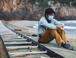 M. Night Shyamalan sits next to a long dolly track on the beach location of OLD (2021)