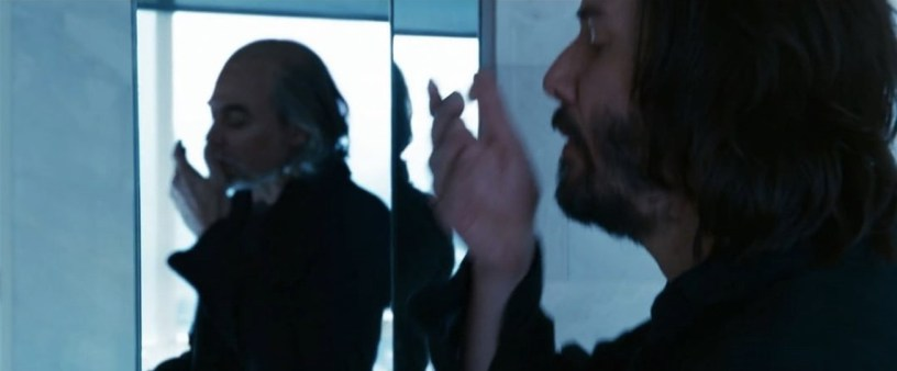 A reflection of an old man is seen in a mirror as Thomas Anderson (Keanu Reeves) takes prescription pills in his bathroom, in THE MATRIX RESURRECTIONS (2021)