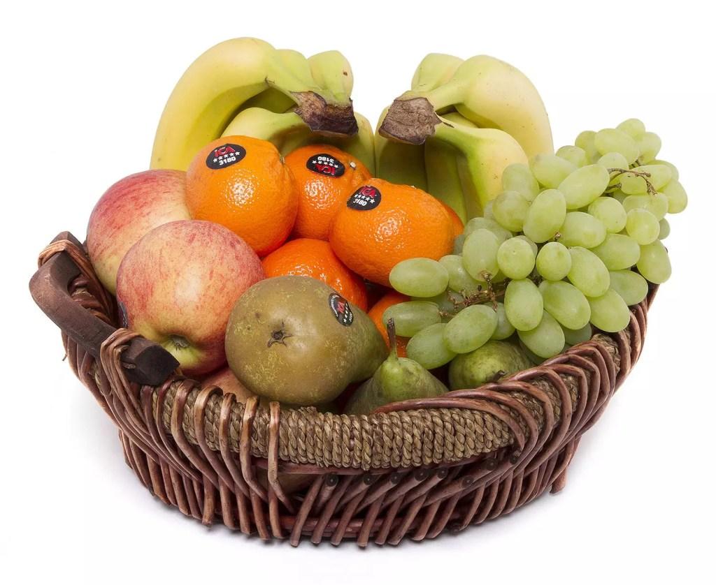 Fruktkorg med bananer, apelsiner, äpple, päron och vindruvor.