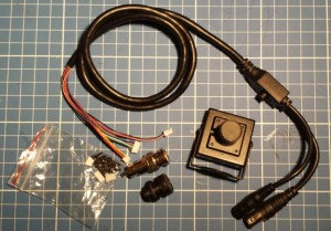 L to R: OSD cable, assorted screws and spare connectors, AV plug, spare lens and Camera