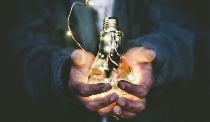 man's hands holding a lit lightbulb