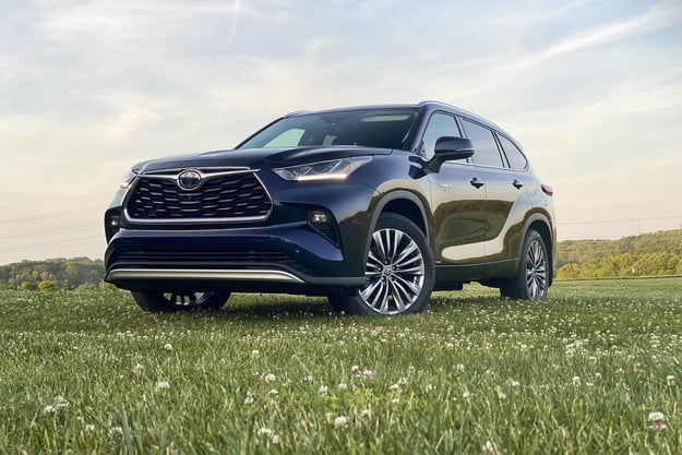 Angled front view of the 2021 Toyota Highlander Hybrid Platinum in a field (driver's side).