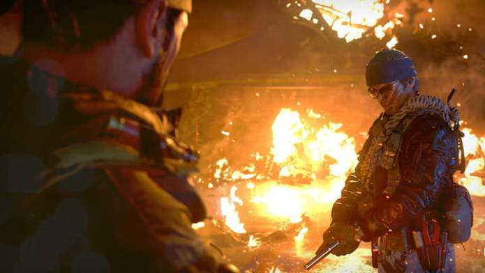 A soldier loading a pistol into a burning building.