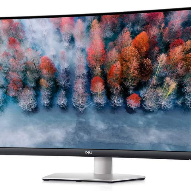 The 32-inch Dell S3221QS curved 4K monitor with a forest scene on the screen.