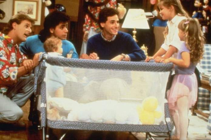 The cast of Full House crowded around a crib.