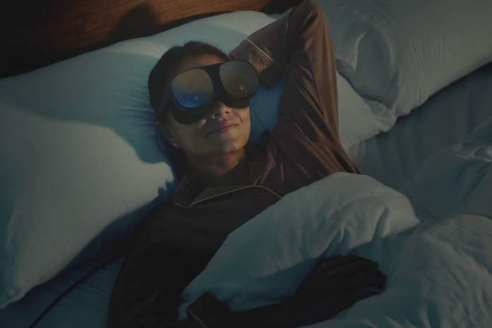 Person lying in bed ready to sleep while wearing an HTC Vive Flow standalone VR headset.