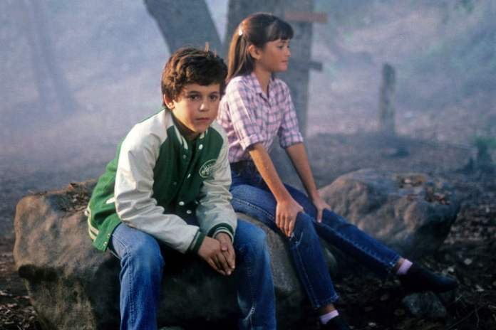 Kevin and Vinnie sitting on a rock in a scene from The Wonder Years.