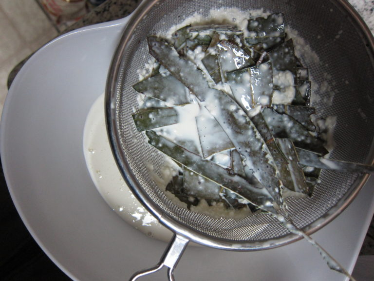 Straining coarsely chopped eucalyptus leaves from a cream mixture