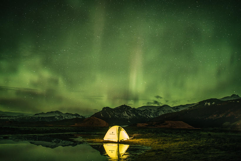 A tent glows against a backdrop of Northern Lights.