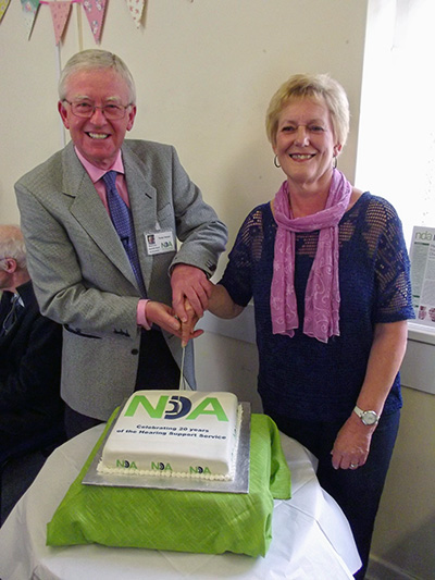tonny-innes-chairman-and-gill-girling-NDA-trustee-and-first-hearing-support-service-vounteer-cut-the-birthday-cake