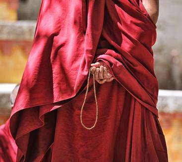 Tibetischer Mönch mit Gebetskette.